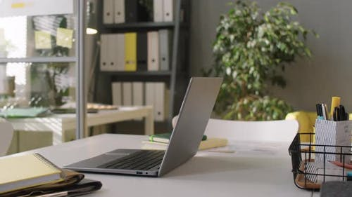 Laptop and Copybooks on Office Desk