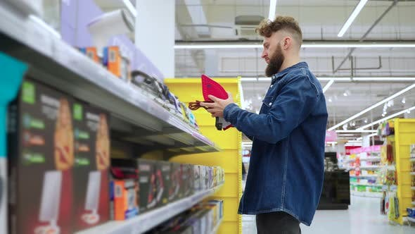 Adult Man is Choosing Iron in Hardware Store