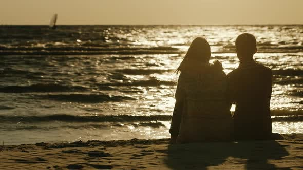 Thumbnail for A Loving Couple Sitting Together on the Sand, Admiring the Sea and the Sunset. Sea Swimming