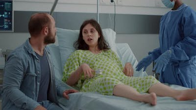 Caucasian Family Expecting Baby in Hospital Ward