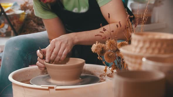 Thumbnail for Pottery - a Man with an Iron Spatula Is Helping Himself Maintaining the Shape of a Bowl