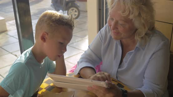 Cover Image for Grandmother and Grandson with Pad in Cafe