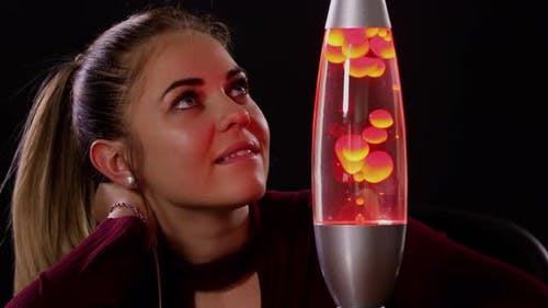 Pretty Woman Looking At A Lava Lamp