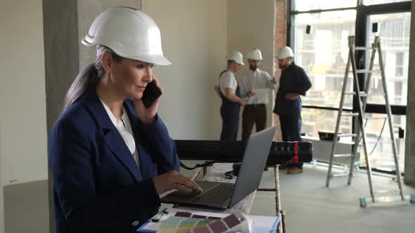 Architect Talking Cellphone During Work on Laptop