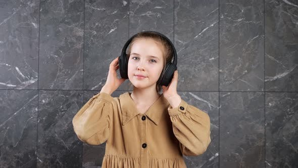 Young Lady in Black Headphones Listens to Music Dancing