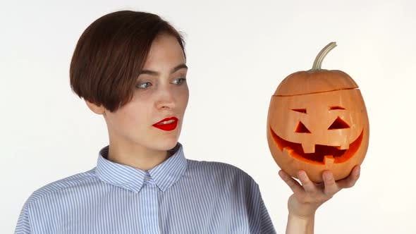 Thumbnail for Young Woman Looking Shocked, Posing with Halloween Carved Pumpkin