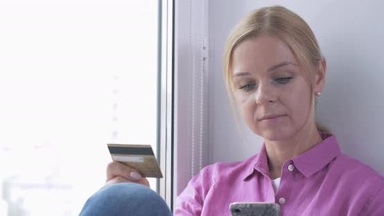 Thumbnail for Portrait of Smiling Woman Holding Credit Card in Her Hand While Shopping Online