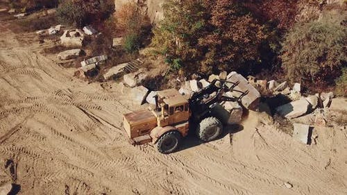 professional bulldozer with a bucket is spreading sand near the stones