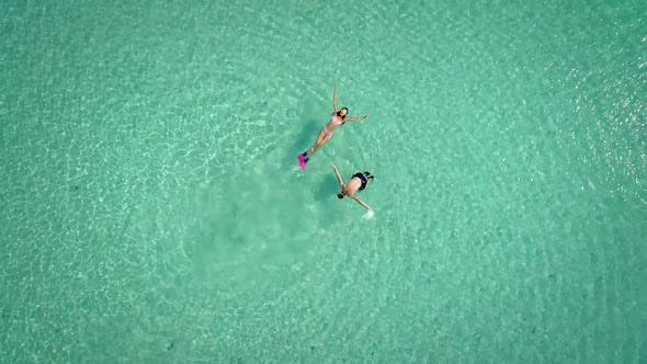 Thumbnail for Aerial view of man and woman with masks and flippers swimming on their backs.