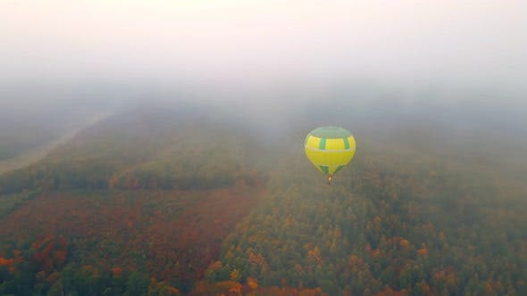Balloon Flying Over the Autumn Forest in Thick Fog and Cloudy Weather, View From Above