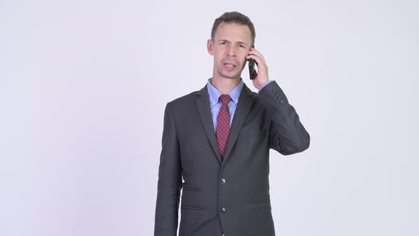 Cover Image for Studio Shot of Angry Businessman Talking on the Phone