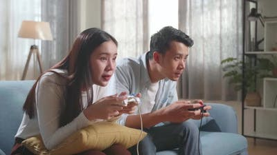 Young Asian Couple Is Playing Video Games At Home