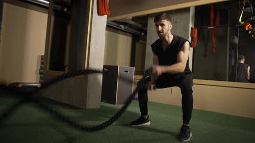Strong Athlete Doing Battle Rope Exercise at Crossfit Gym