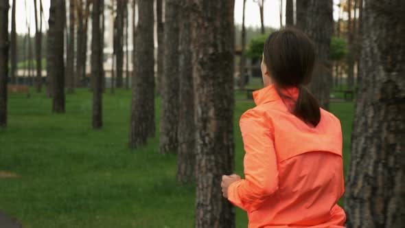 Thumbnail for Brunette female in orange jacket running on footpath in the city park