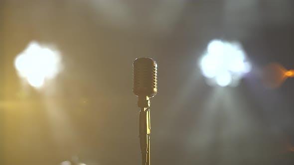 Klassisches Retro Chrom Mikrofon in dunklem Studio mit Rauch- und Neonbeleuchtung. Dynamische Neonbeleuchtung