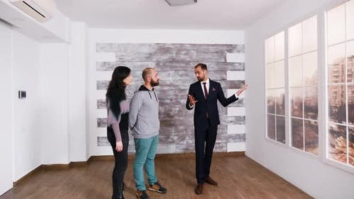 Successful Real Estate Agent Talking with Young Couple