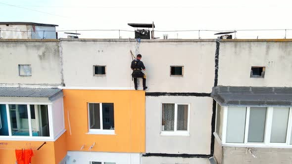 Worker Go Down To a Construction Site of a High-rise Building. Dangerous Work in High-altitude
