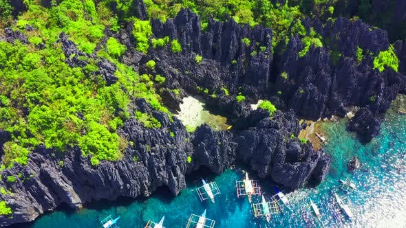 Thumbnail for Aerial Drone View of Swimmers Inside a Tiny Hidden Tropical Lagoon Surrounded By Cliffs - Secret