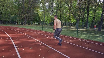 Sport man running on racetrack, View of athletic shirtless sportsman running on track