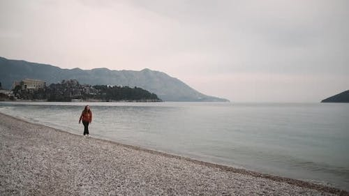 Lonely Young woman walks along the sea in spring cloudy weather