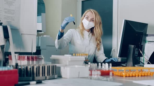 A Microbiology Scientist Checks Test Tubes in the Laboratory and Enters Information Into a Database