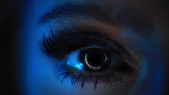 Thumbnail for Close up of a woman's eye with beautiful make up opening in a dark blue lighting