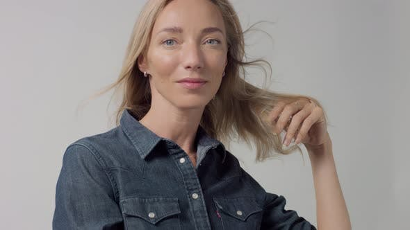 Thumbnail for Young Beauty Blonde Woman in Studio Wears Classic Denim with Blowing Hair