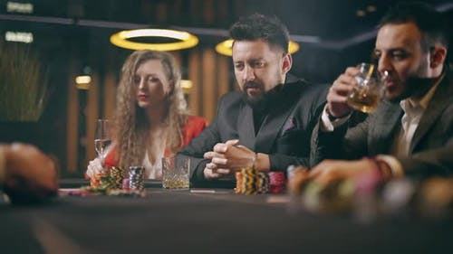 A Holdem Dealer is Distributing of Cards in a Casino