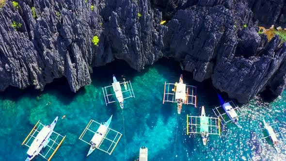 Cover Image for Aerial Drone View of Swimmers Inside a Tiny Hidden Tropical Lagoon Surrounded By Cliffs - Secret