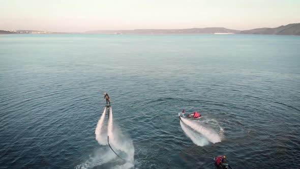 Thumbnail for Sportive People Flying Over Water with Jet Packs