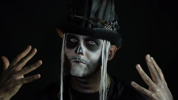 Man in Skeleton Halloween Cosplay Costume. Guy in Creepy Skull Makeup Making Faces, Looks Mysterious