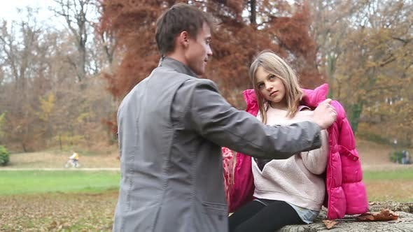 Thumbnail for Father helping daughter put on jacket and scarf in the park