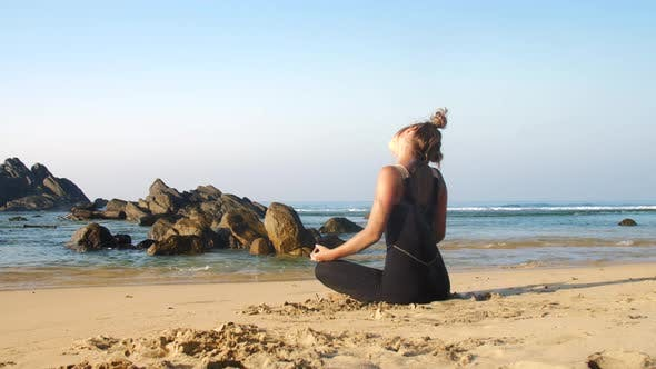 Thumbnail for Sporty Girl Stretches Neck at Blue Ocean with Brown Rocks
