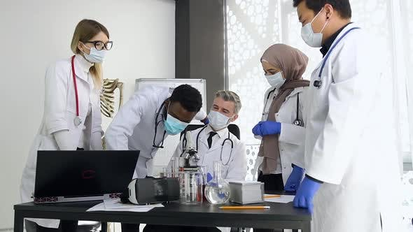Thumbnail for Doctor With His Concentrated Mixed Race Doctors-Colleagues Working Together with Microscope