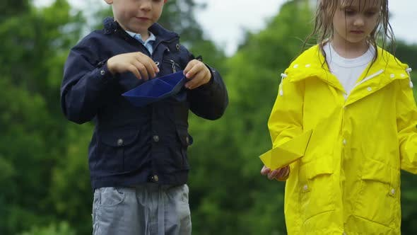 Thumbnail for Children with Paper Boats Standing in Puddle