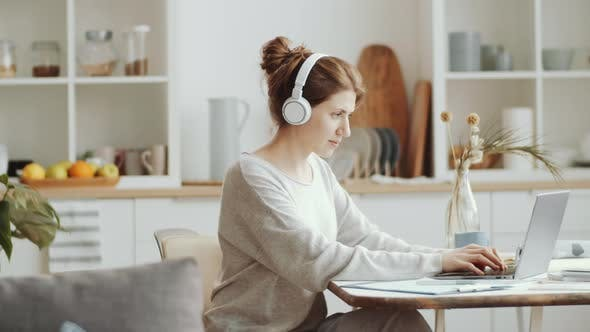 Thumbnail for Woman in Wireless Headphones Working on Laptop at Home
