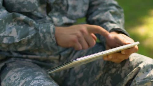 Soldier Using Tablet Outdoors, Online Psychological Support Service for Veterans