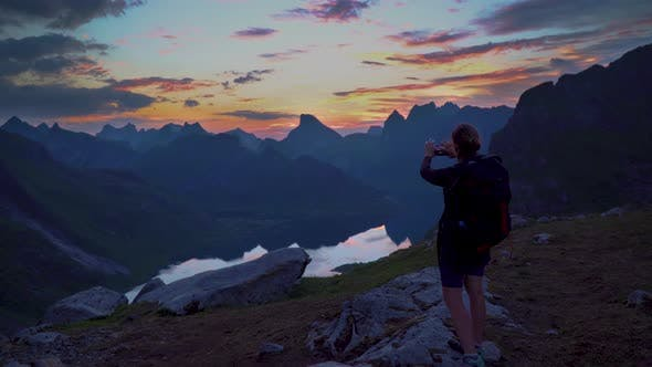 Thumbnail for Hiker Reaches Mountain Peak, Takes Picture of Sunset