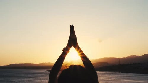 Young Woman Meditating on a Beautiful Golden Sunset. Caucasian Girl Practicing Yoga. Sport and