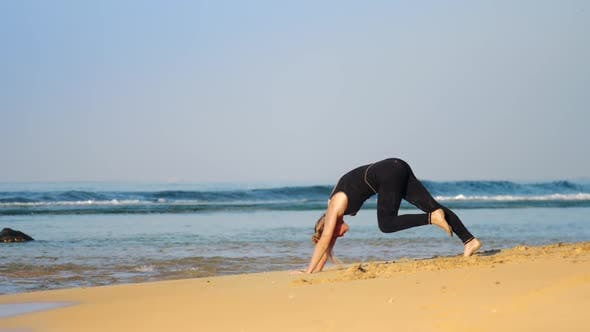 Thumbnail for Girl in Tracksuit Does Pilates Exercises on Ocean Beach