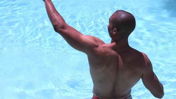African American man standing in swimming pool and dunking under