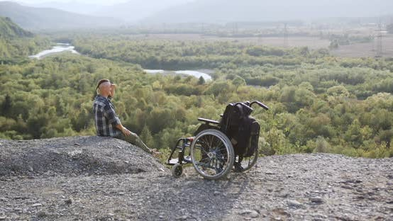 Thumbnail for Guy with Motionless Legs After Accident Sitting Near Wheelchair on the Top of the Hill