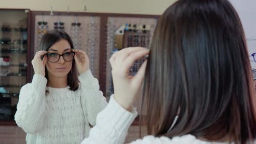 Young Brunette with Blue Eyes in a Cozy White Sweater Trying on Glasses in Front of a Mirror in an