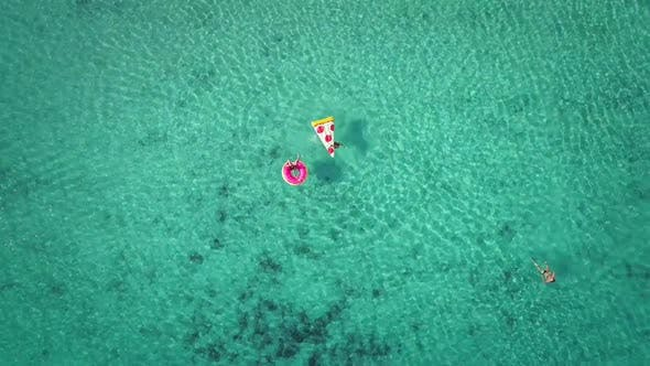 Thumbnail for Close aerial view of two young girls swimming and playing in sea with inflatables.
