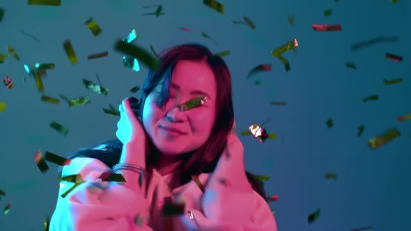 Excited Asian Attractive Woman Dancing, Having Fun, Rejoices Over Confetti Rain with Neon Light in