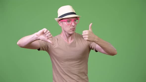 Thumbnail for Young Handsome Tourist Man Choosing Between Thumbs Up and Thumbs Down