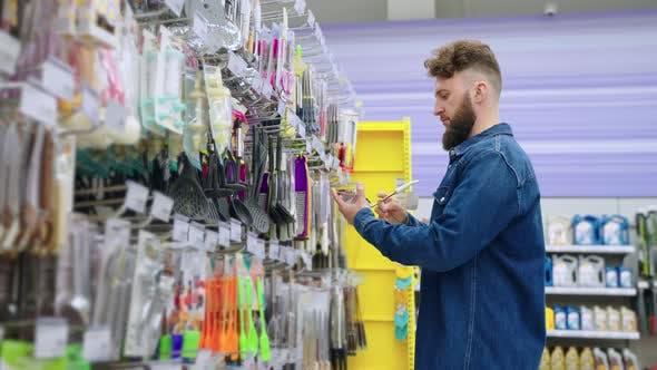 Man Buying Kitchen Utensils in Homeware Store