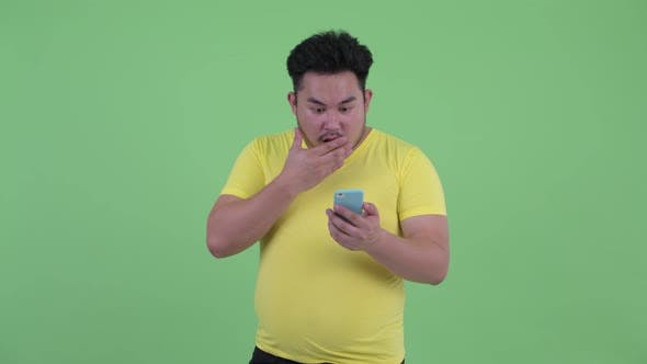 Cover Image for Happy Young Overweight Asian Man Using Phone and Looking Surprised