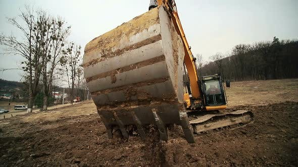 Thumbnail for Close-up of a Excavator Bucket That Throws Out the Earth. Slow Motion of a Digger Digging a Pit and