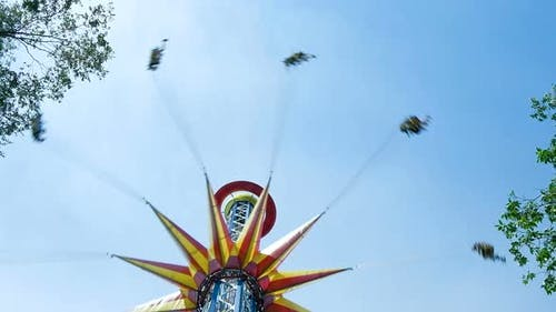 Colourful Sky Flyer Rotates People Under Clear Blue Sky